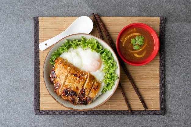 Hühnchenreis oder teriyaki-hühnchen-ei-onsen in grauer schüssel mit austernsauce auf dem tisch.