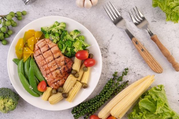 Hühnchensteak mit weißem sesam, erbsen, tomaten, brokkoli und kürbis in einem weißen teller.
