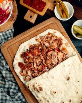 Hühner-döner-kebab im fladenbrot, serviert mit eingelegter gurke und pfeffer