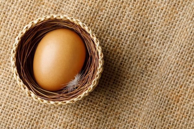 Hühner- oder hühnerei im weidenkorb auf sackleinen