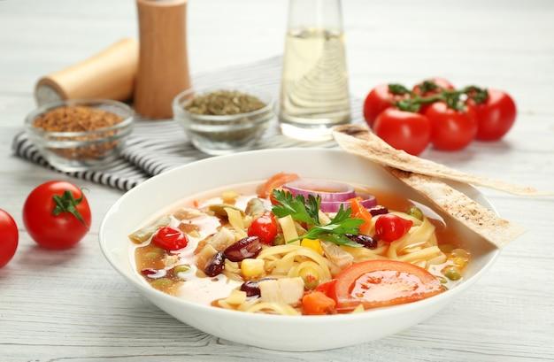 Hühner-tortilla-suppe im teller auf holztisch