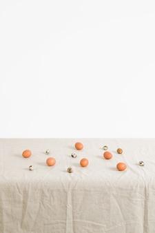 Hühner- und wachteleier auf einer weißen tischdecke
