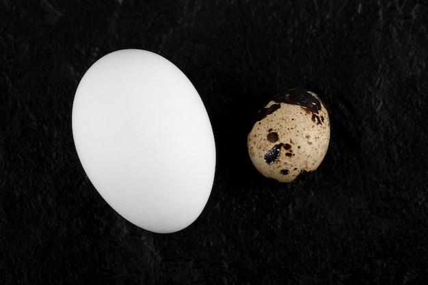 Hühner- und wachteleier auf schwarzer oberfläche.