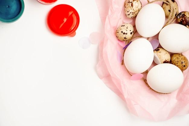 Hühner- und wachteleier nisten und malen auf weißem hintergrund glücklichem ostern-handwerkskonzept