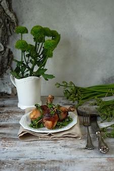 Hühnerbeine im speck und im gebratenen adlerfarn auf einer weinleseplatte.