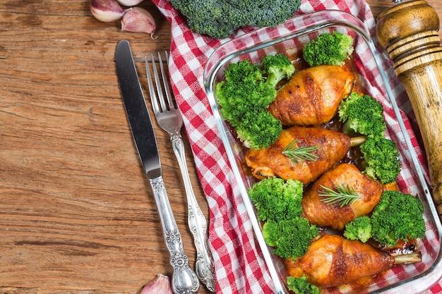 Hühnerbeine mit gemüse auf holztisch.