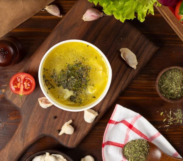 Hühnerbrühe mit kräutersuppe in der wegwerfschalenschüssel diente mit grünem gemüse.