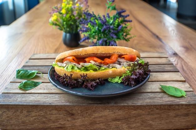 Hühnerbrust geräucherter lachs auf roggenbrot-sandwich auf holztisch