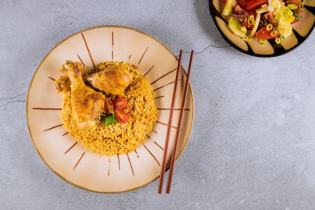Hühnerbrust mit gebratenem reis auf einer platte mit essstäbchen
