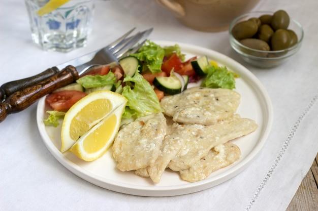 Hühnerbrust mit sahne aus milch und zitrone, serviert mit einem salat aus frischem gemüse.