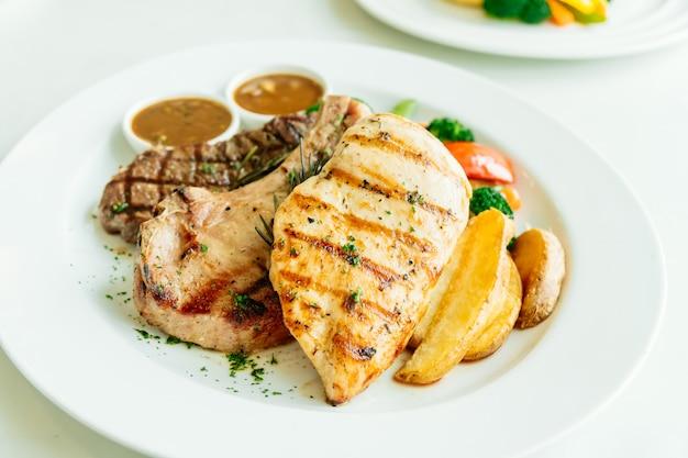 Hühnerbrust und schweinekotelett mit rindfleischsteak und gemüse