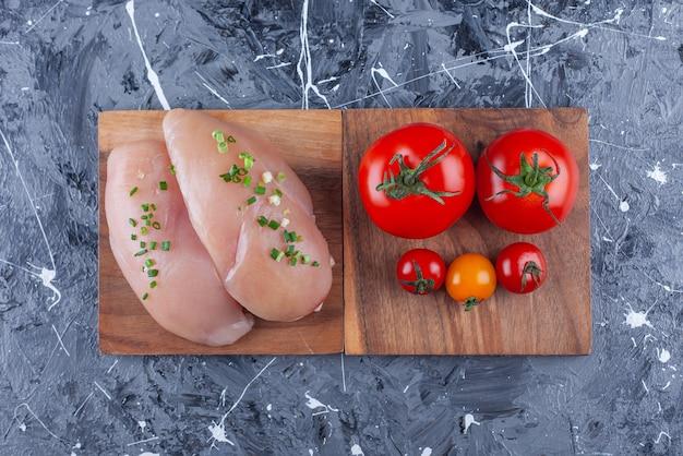Hühnerbrust und tomaten auf einem brett auf der blauen oberfläche