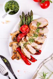 Hühnerbrustgrill mit grillgemüse und pestosoße in einer platte auf holz