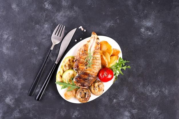 Hühnerbrustgrill mit grillgemüse und pestosoße in einer platte