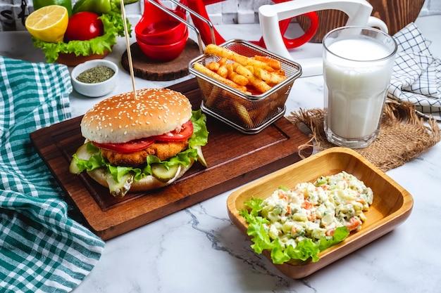 Hühnerburger mit pommes frites auf einem brett, einem hauptsalat und einem glas joghurt