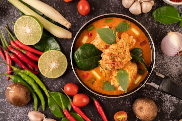 Hühnercurry in einer pfanne mit zitronengras, kaffirlimettenblättern, tomaten, zitrone und knoblauch