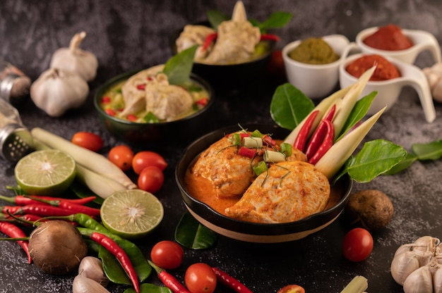 Hühnercurry in einer schüssel mit zitronengras, kaffirlimettenblättern, tomaten, zitrone und knoblauch