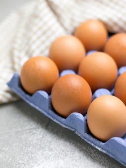Hühnereier im blauen karton auf grauem steintisch