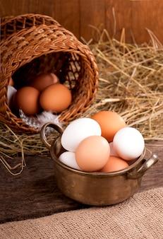 Hühnereier im korb auf grauem hölzernem hintergrund