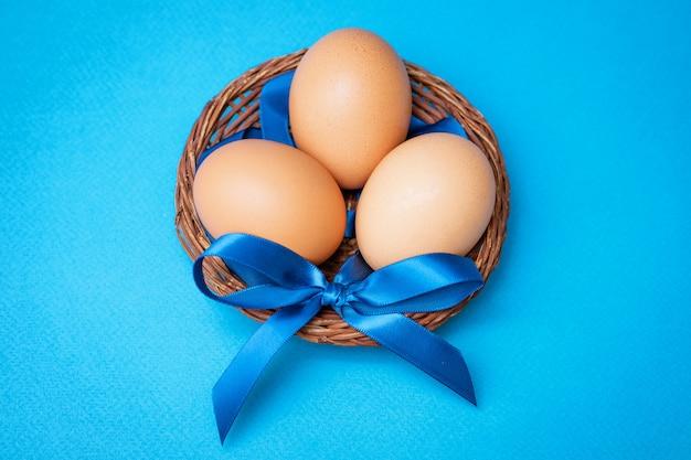 Hühnereier in der strohschale mit einem blauen bogen auf einem blauen hintergrund, copyspace.