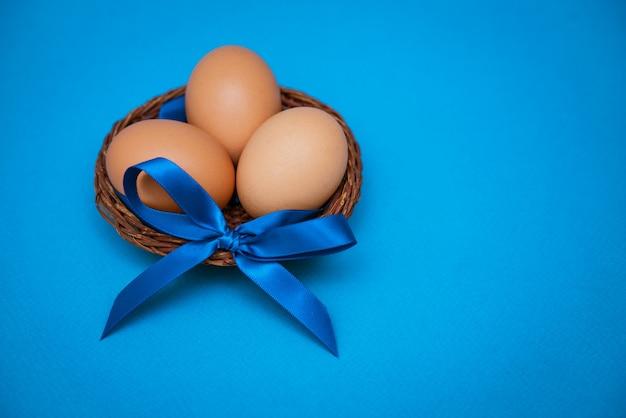 Hühnereier in der strohschale mit einer blauen schleife auf einem blauen hintergrund,