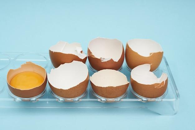 Hühnereier in einem eierhalter. volles tablett mit eiern. ein halbes ei, eigelb, schale.