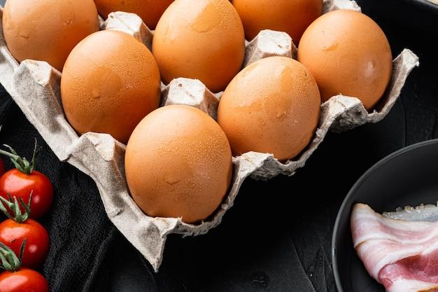 Hühnereier in einem eierkartontablettsatz auf schwarzem hintergrund
