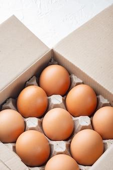 Hühnereier in einem eierkartontablettsatz auf weißem hintergrund