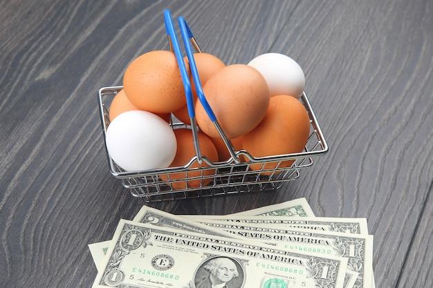 Hühnereier in einem supermarkt-einkaufskorb auf einem holztisch. verkauf und geschäft von lebensmitteln