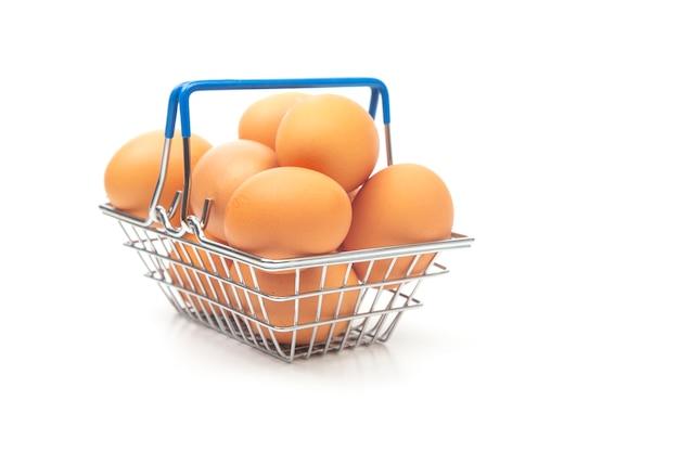 Hühnereier in einem supermarkt-einkaufskorb auf einem weißen hintergrund.