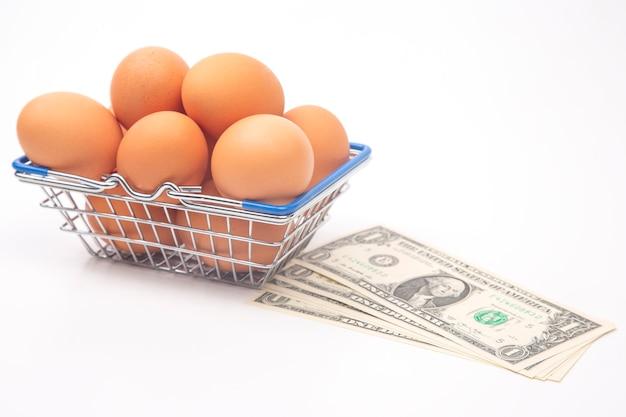 Hühnereier in einem supermarkt-einkaufskorb und dollars auf einem weißen hintergrund. verkauf und geschäft von lebensmitteln