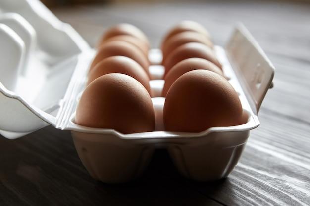 Hühnereier in einem weißen behälter auf einem braunen holztisch