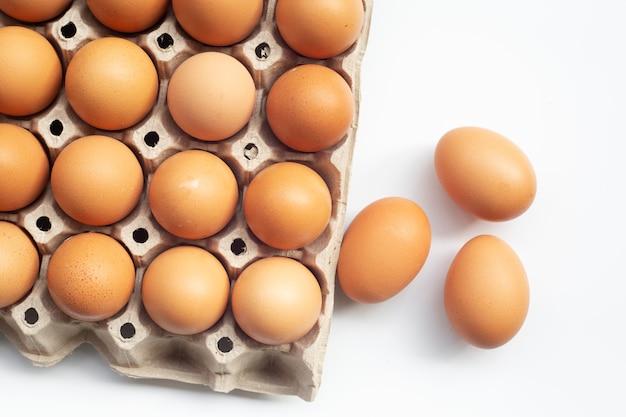 Hühnereier in einer schale auf weißem hintergrund mit draufsicht.