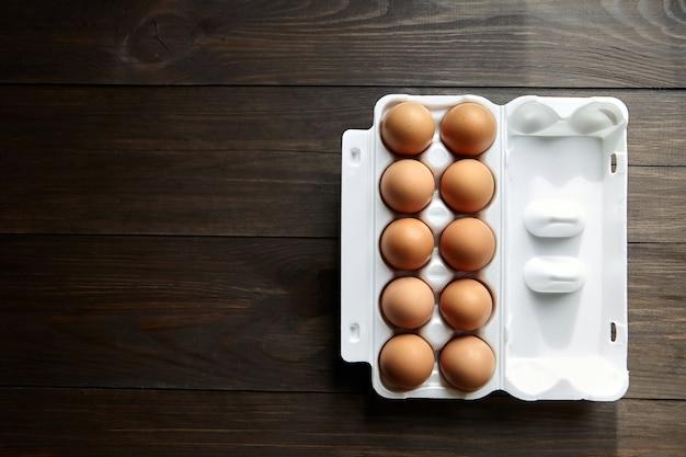 Hühnereier in einer weißen schachtel auf einem braunen holztisch