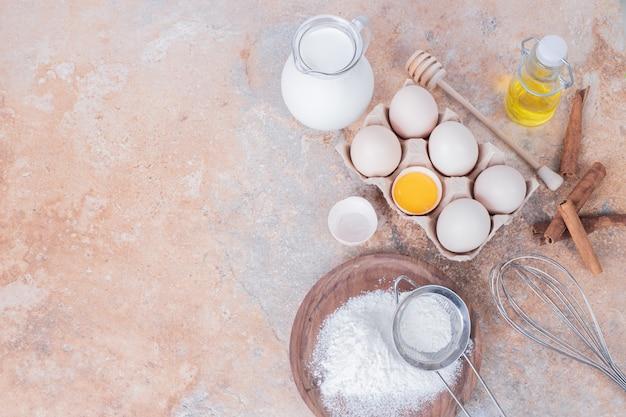 Hühnereier, milch, mehl und gewürze auf marmoroberfläche.
