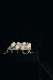 Hühnereier mit federn im behälter zwischen schwärze