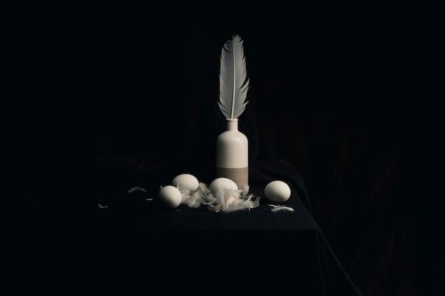 Hühnereier mit federn in der nähe der spule in der vase am rand der tabelle zwischen schwärze