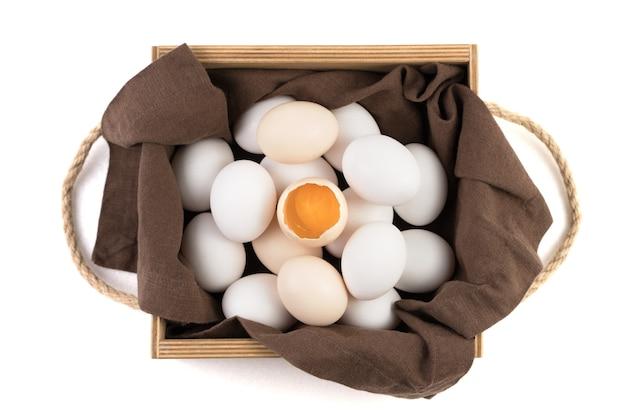 Hühnereier sind weiß und braun mit einem zerbrochenen ei in der mitte, in dem ein frisches eigelb sichtbar ist.