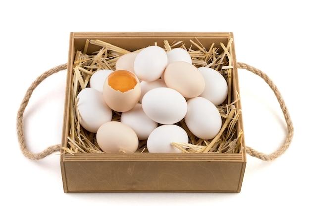 Hühnereier von weißer und brauner farbe mit einem zerbrochenen ei in der mitte.