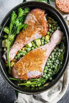 Hühnereintopf. rezept für trommelstöcke mit petersilie, erbsen, sellerie und kartoffeln. ansicht von oben.