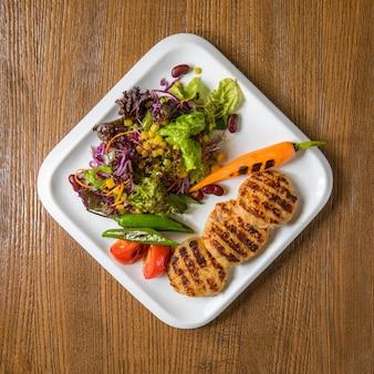 Hühnerfiletcotlets der draufsicht mit grünem salat und karotte.