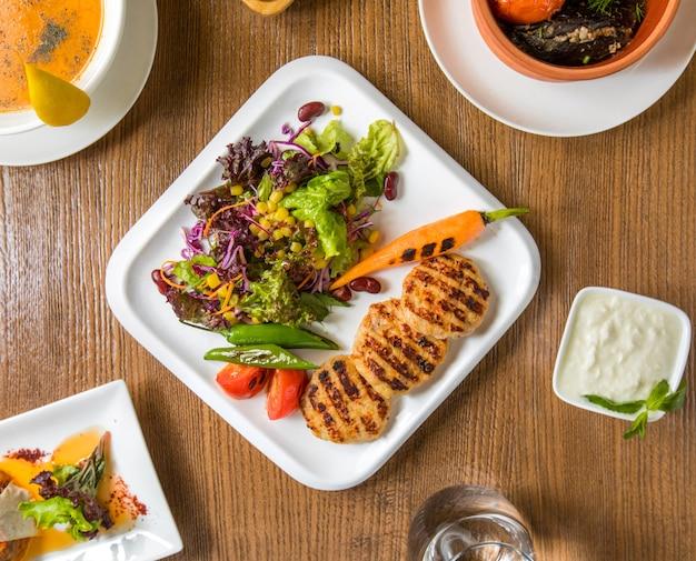 Hühnerfiletcotlets und -salat der draufsicht mit joghurt.