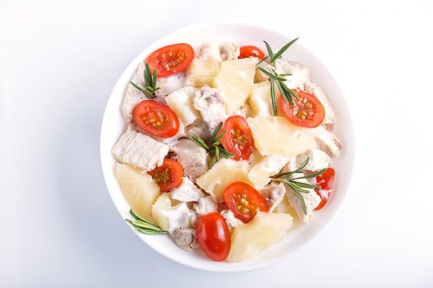 Hühnerfiletsalat mit den rosmarin-, ananas- und kirschtomaten lokalisiert auf weiß