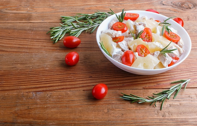 Hühnerfiletsalat mit rosmarin-, ananas- und kirschtomaten auf braunem holz