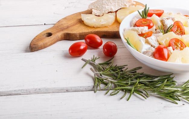 Hühnerfiletsalat mit rosmarin-, ananas- und kirschtomaten auf weißer holzoberfläche.