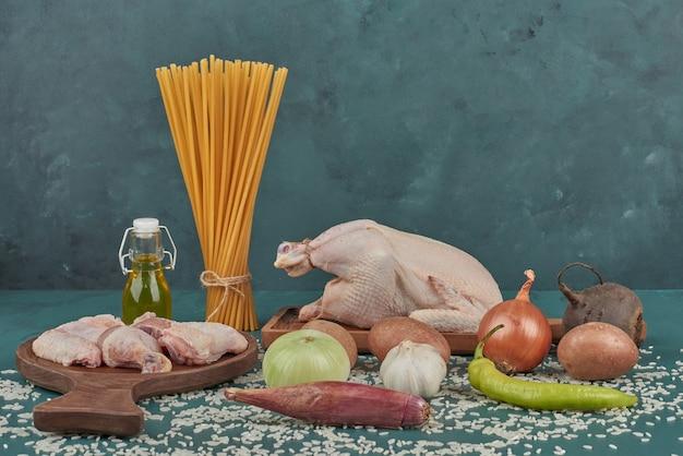 Hühnerfleisch auf einem holzbrett mit nudeln und gemüse herum.