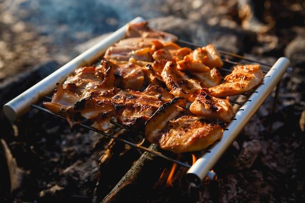 Hühnerfleisch im feuerlager. tragbares edelstahl-grillgrill-wanderkonzept. kochen auf wilder natur.