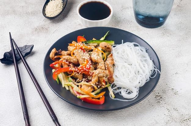 Hühnerfleisch mit gemüse-wok und chinesischen reisnudeln, saucen und sesam in einer schwarzen schüssel mit