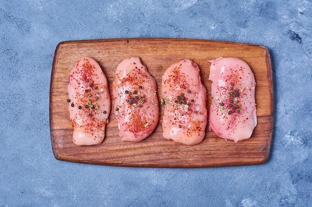 Hühnerfleisch mit gewürzen auf einem holzbrett auf blau