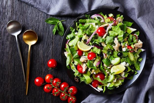 Hühnerfleisch, oliven, rote zwiebeln, tomaten, gurken, minze, salatsalat, bestreut mit zerbröckeltem feta-käse auf einem schwarzen teller, horizontale ansicht von oben, flach liegen